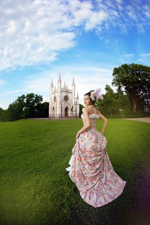 prinzessin: Eine Frau wie eine Prinzessin in einem Vintage-Kleid vor dem Zauberschloss