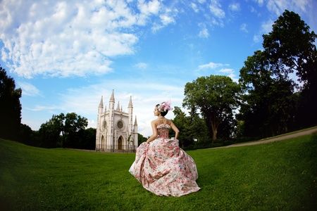 fairytale castle: A woman like a princess in an vintage dress before the magic castle