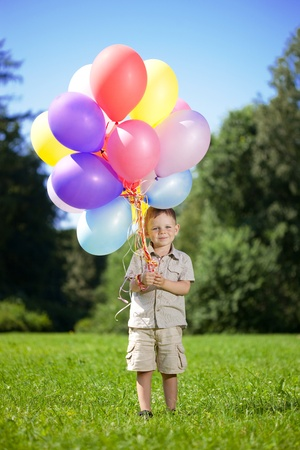 The image of a child with a bunch of balloons in their hands photo