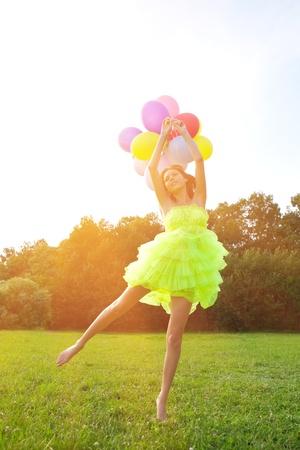 Brillante mujer feliz colgando del racimo de globos de aire de colores Foto de archivo