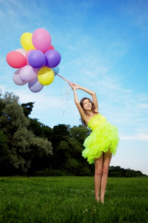 yellow dress: Bright happy woman holding bunch of colorful air balloons