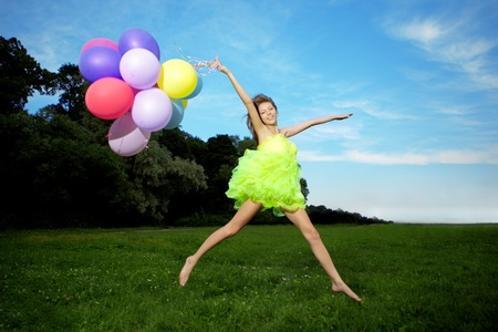colorful dress: Bright happy woman holding bunch of colorful air balloons