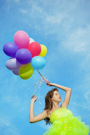 Bright happy woman holding bunch of colorful air balloons  photo