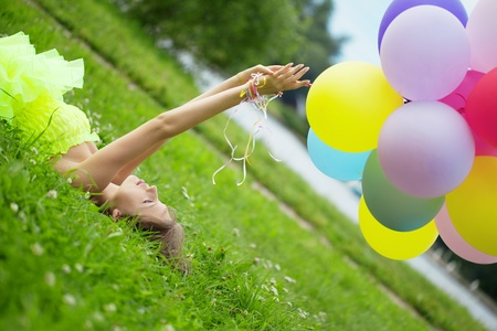 Bright happy woman holding bunch of colorful air balloons Banco de Imagens