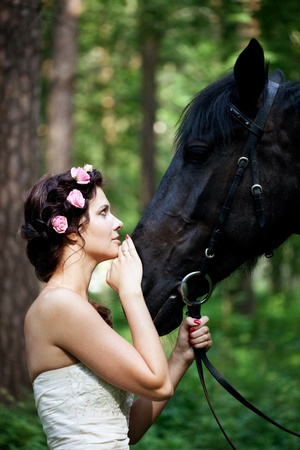 Beautiful woman and a dark horse photo