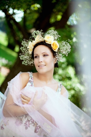 Beautiful woman with a wreath of roses on her head photo