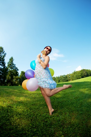 lollipops: The bright woman in sunglasses with balloons and candy