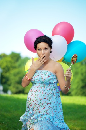 Pregnant girl with balloons in the park photo