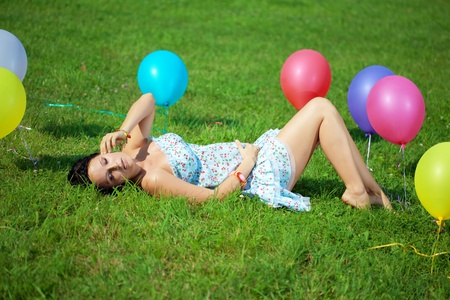 Pregnant woman with balloons in the park on grass photo