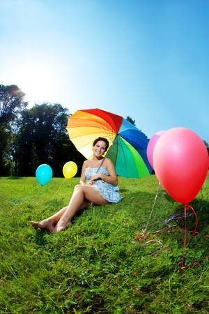 Pregnant woman with balloons in the park with a rainbow umbrella photo