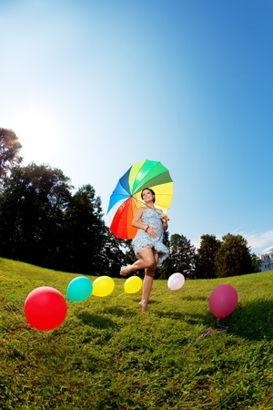 rainbow umbrella: Pregnant woman with balloons in the park with a rainbow umbrella