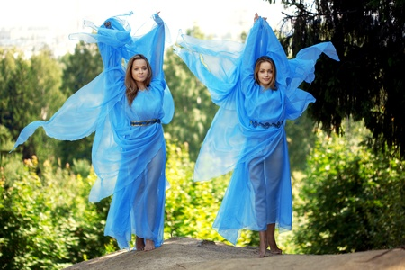 Two woman, twins in the forest in a blue flowing dress photo