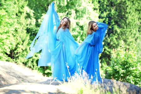 Two twins in the forest in a blue flowing dress photo