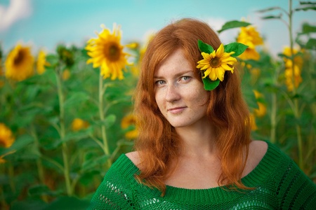 Beautiful red-haired woman with sunflowers photo