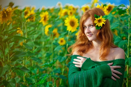 freckles: Beautiful red-haired woman with sunflowers Stock Photo