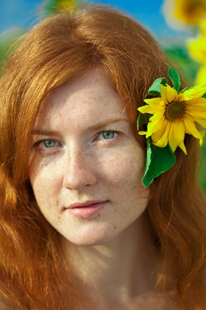 redhead: Beautiful red-haired woman with sunflowers Stock Photo