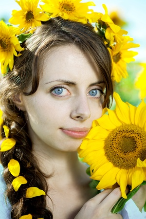 Woman with big blue eyes in a field of sunflowers photo