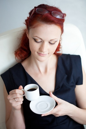 secretary desk: Beautiful redheaded woman in the workplace with a cup of coffee