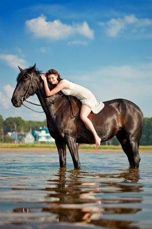 horse riding: Image of a woman on a horse by the sea