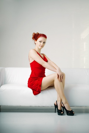 girl in red dress: Luxurious redhead woman in a red dress on white couch Stock Photo