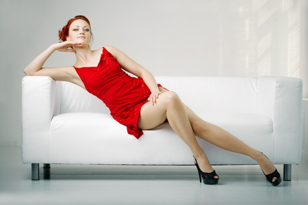 modern sofa: Luxurious redhead woman in a red dress on white couch Stock Photo