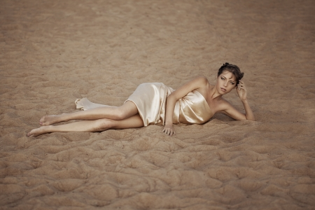 Picture of woman in flying gold cloth in the sand photo