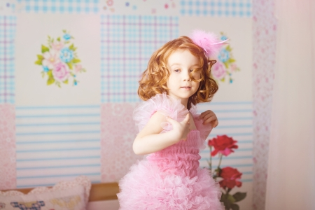 The image of girl in the nursery in pink dress photo