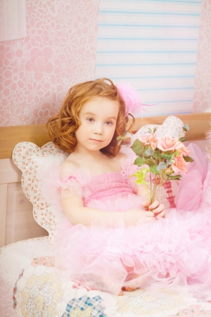 The image of girl in the nursery in pink dresses photo