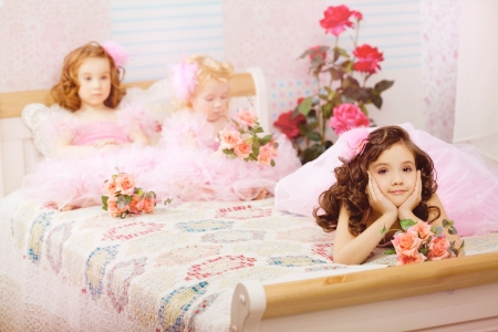 child in bed: The image of children in the nursery in pink dresses Stock Photo
