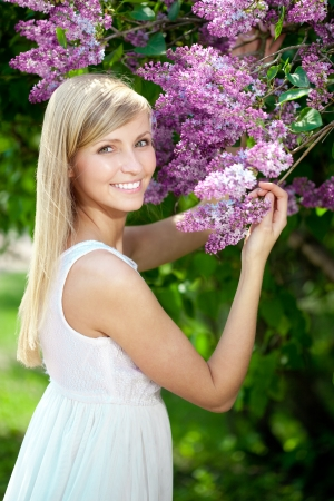 Portret of smiling beautiful woman with violet flowers photo