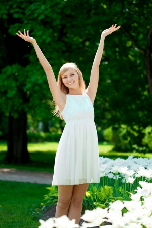 Young beautiful smiling woman with arms raised outdoors  photo