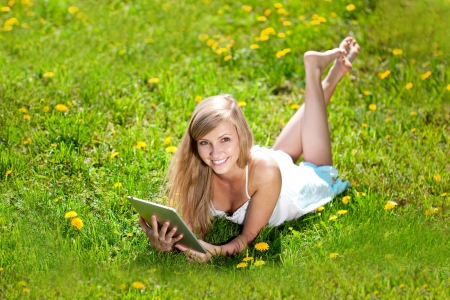 Portrait of young beautiful smiling woman with tablet pc, outdoors  photo