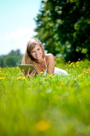 Portrait of young beautiful smiling woman with tablet pc, outdoors