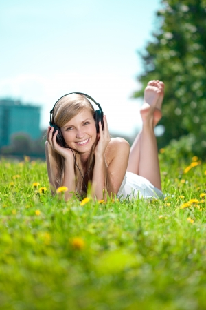 Beautiful smiling woman Woman listening to music on headphones outdoors photo