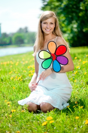 Beautiful smiling woman with a rainbow flower outdoors  photo