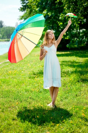 Beautiful smiling woman with two rainbow umbrellas, outdoors photo