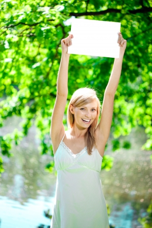 Young beautiful smiling woman with blank poster  outdoors Stock Photo - 14644708
