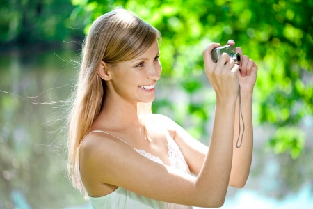 Beautiful smiling woman with a camera in his hands, outdoors  photo