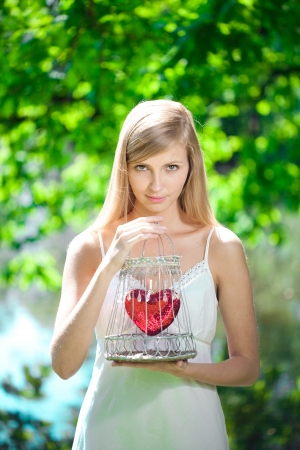 love expression: Beautiful sad woman with a heart in a cage Stock Photo