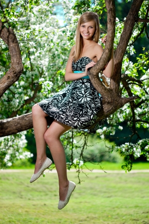 Smiling beautiful woman and flowering tree photo