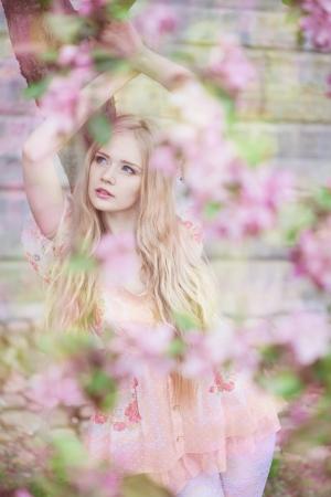 Beautiful woman with flowering tree drinking tea  photo