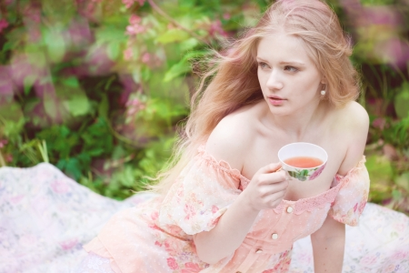 Beautiful woman with flowering tree drinking tea photo