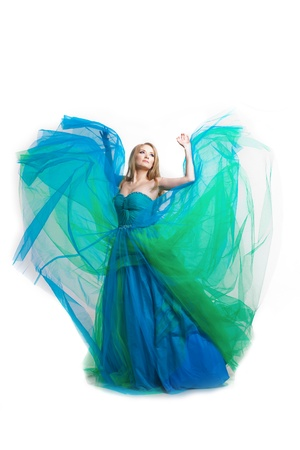 windblown: Stylish woman in a blue dress on a white background