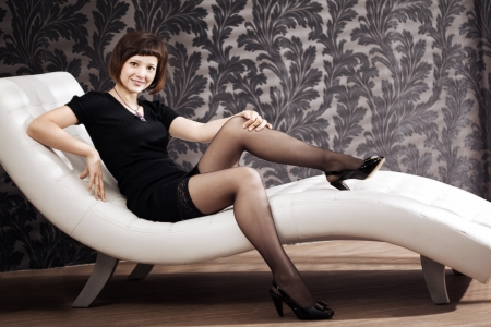 Beautiful woman is sitting on the couch photo