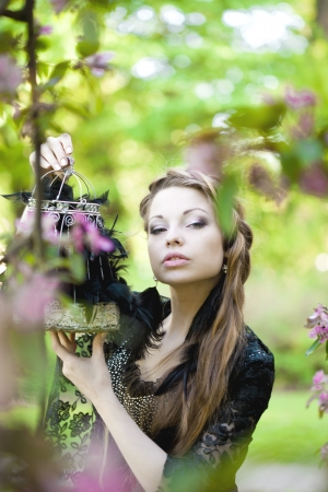 Beautiful Witch with a strange cage in his hands photo