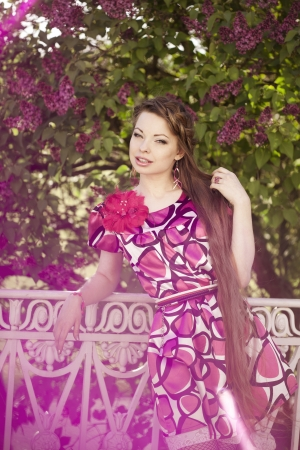 Beautiful woman with a hair braid and stylish make up on the background of a blossoming park. photo