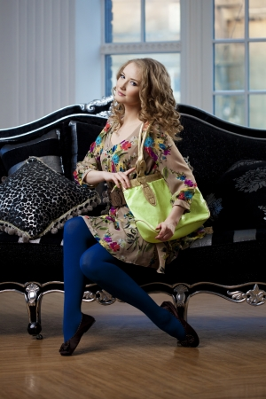 luxurious sofa: Beautiful woman in luxurious sofa with handbag Stock Photo