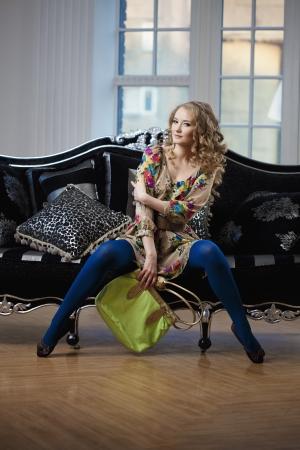 Beautiful woman in luxurious sofa with handbag photo