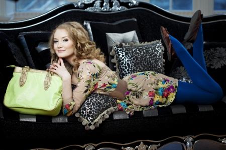 poses de modelos: Mujer hermosa en el sof� con el bolso de lujo