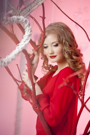 Luxury young woman in red and with red lipstick photo